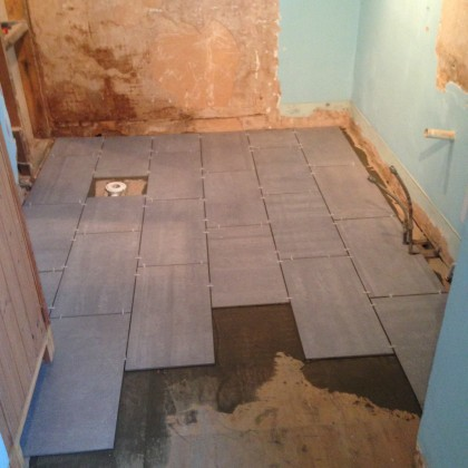 Carefully fitting new slate floor tiles