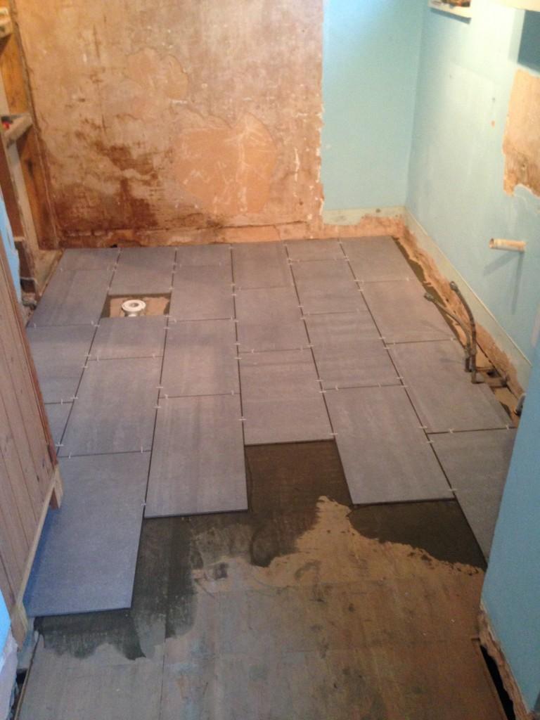 Carefully fitting new slate floor tiles