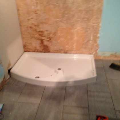 Existing shower tray being refitted on top of new tiled floor